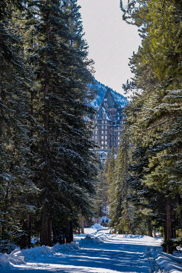 A Peek at the Banff Springs Hotel Through the Forest. Is Seen From a Road That Leads to the Hotel royalty free stock image