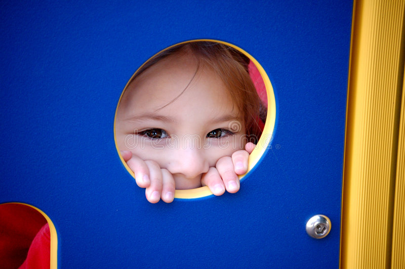 Peek a Boo. Four year old girl peeking through a hole in a playground stock photo