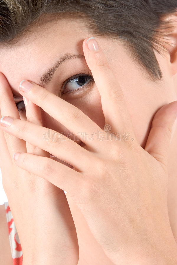 Peek-a-boo. Young woman peeks through her fingers stock image