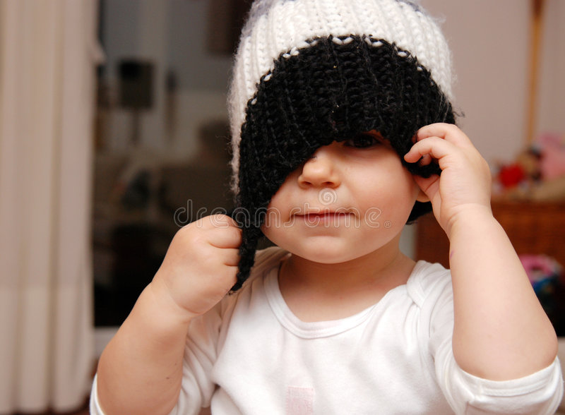 Peek-a-boo. A little girl playing with a knit hat royalty free stock photography