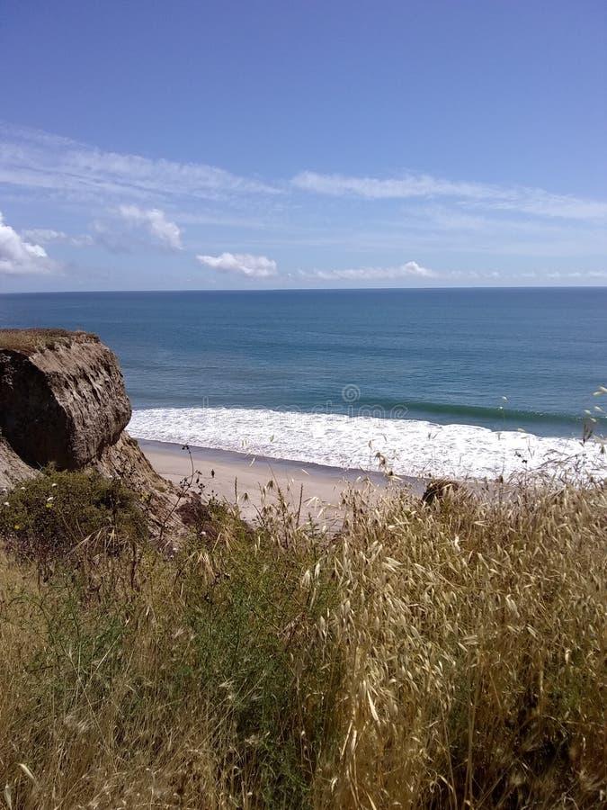 Peek of the cliff. Cliffs, beach, ocean stock photo