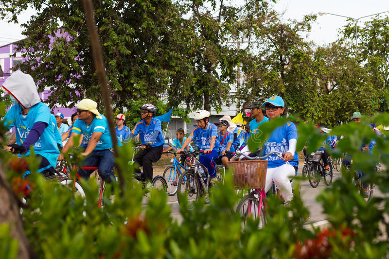 Peek crowd cyclists. PHICHIT THAILAND-AUGUST 19:Peek through the foliage blur to people who are cyclists on the road in activity Bike for mom.On August 19, 2015 stock photography