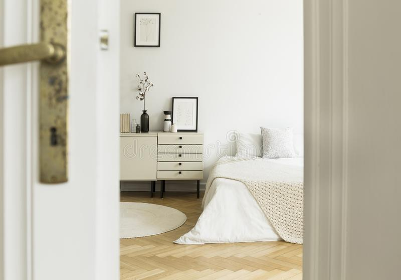 A peek through a door into a monochromatic, white bedroom interior with a bed and cabinets standing on a wooden floor. Real photo. Concept stock images