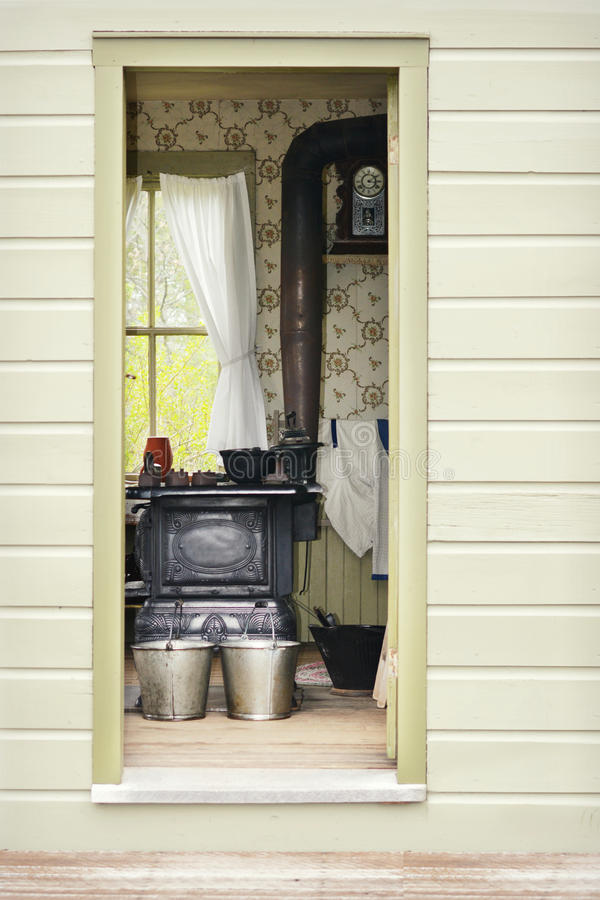 Peek into the Past. A peek into the past looking into the doorway of an Irish Washerwoman's vintage kitchen with an old cast iron stove and tin buckets in front stock images