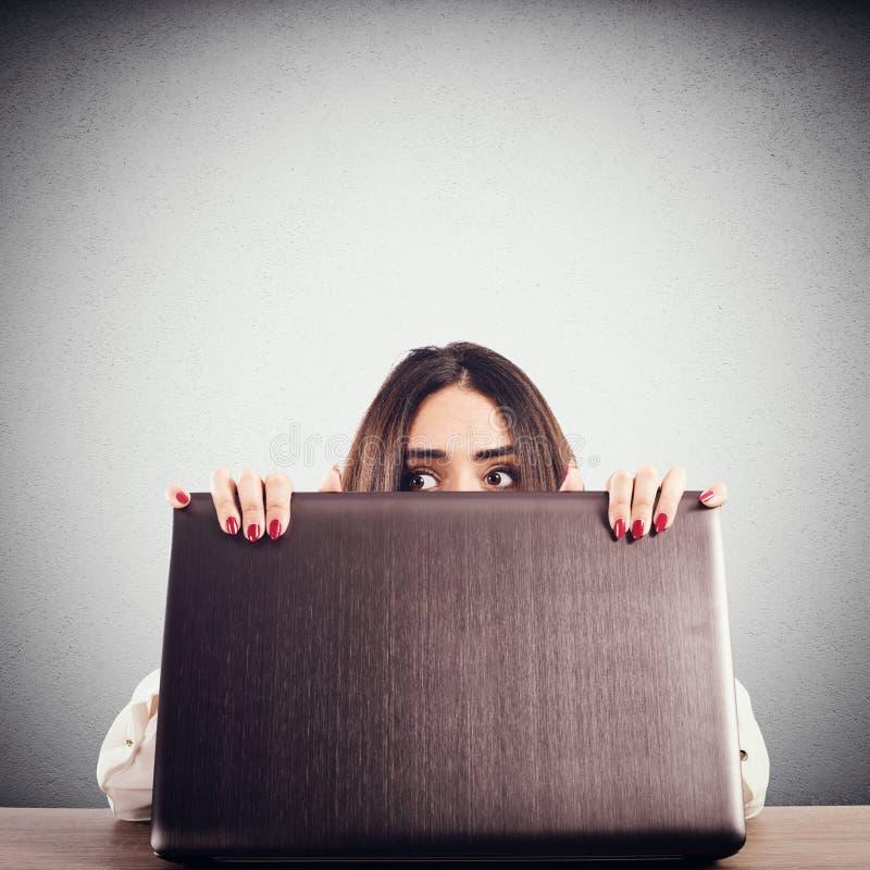 Peek secretly. Woman hidden behind the computer screen peeks secretly stock images
