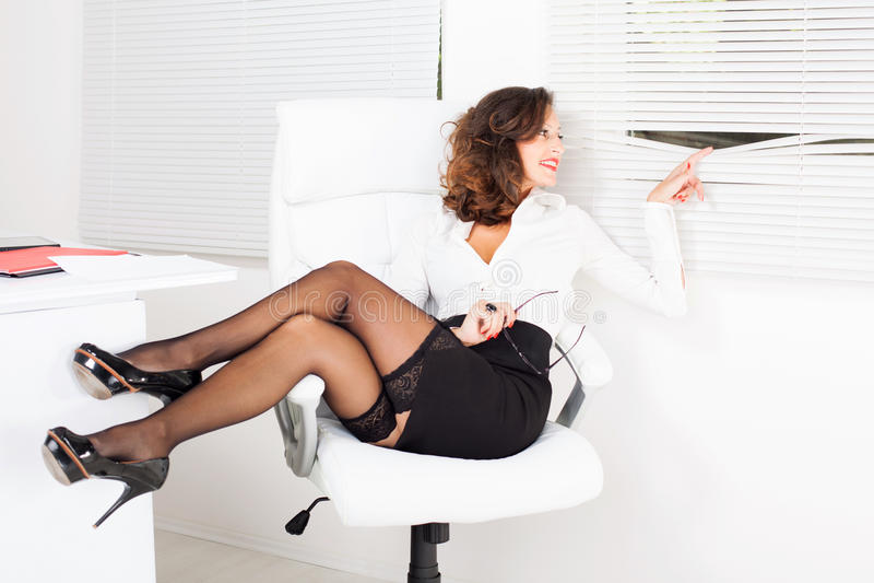 Peek through the window. Business woman sitting on office chair and peek through the window royalty free stock photo