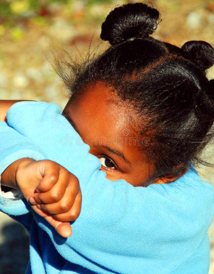 Peekaboo. A young black girl plays peek a boo with the camera by only showing one eye royalty free stock image