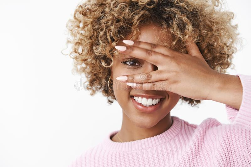 Peeking at future with optimistic gaze. Portrait of good-looking sensual and enthusiastic african american woman with. Curly blond hair close eyes and looking stock image