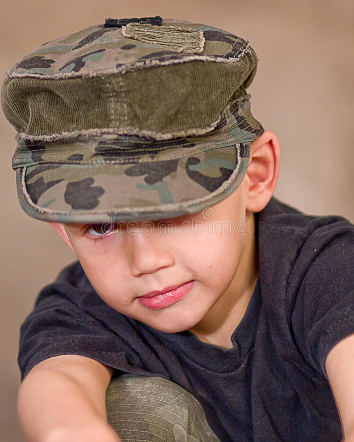 Peeking Under Hat. Young boy peeking under his army hat stock images