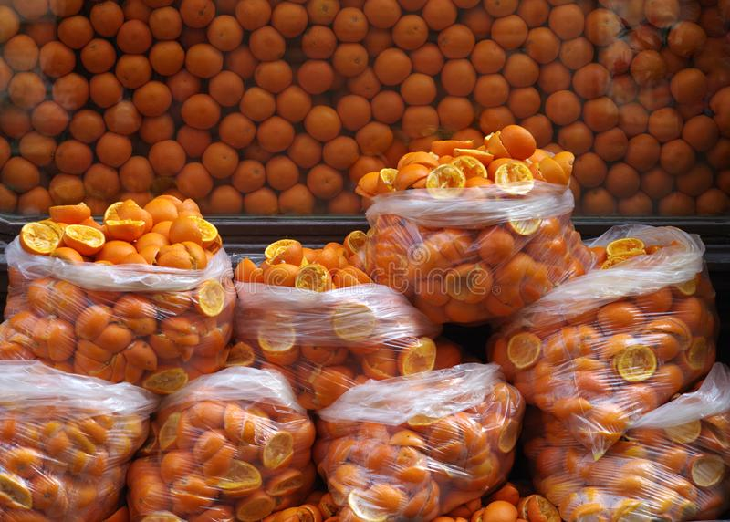 Peel squeezed for the juice of oranges in plastic bags on the background of a large number of fresh oranges.  royalty free stock images