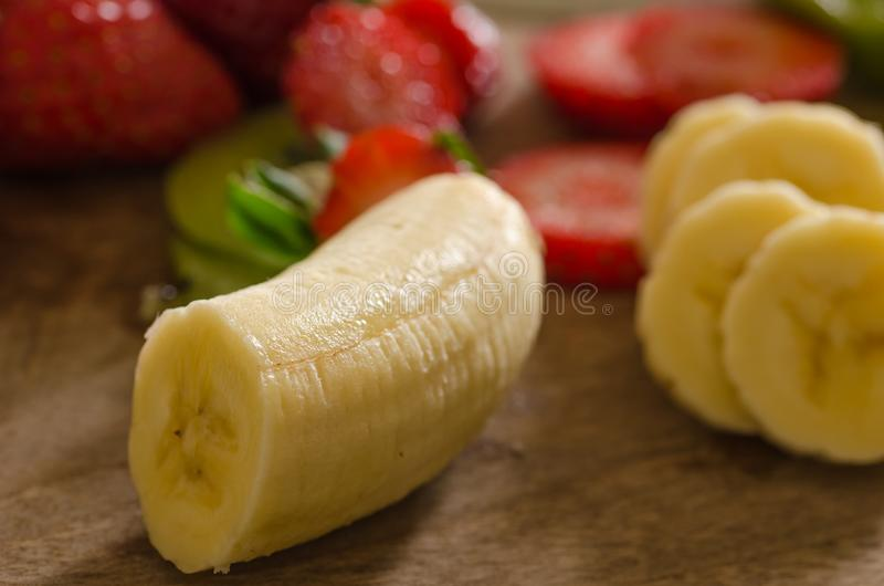 Peeled bananas and sliced strawberries on a wooden floor. Peeled bananas and sliced strawberries on a wooden table.Red and yellow fresh fruit stock image