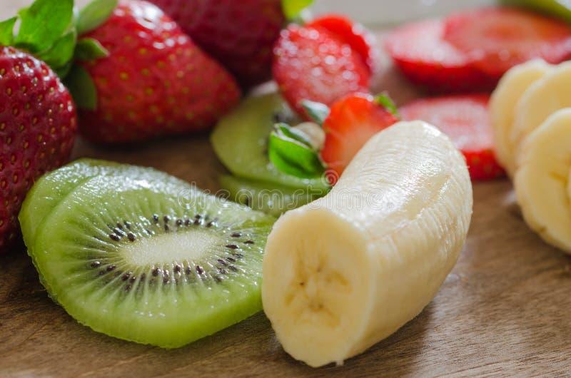 Peeled bananas, sliced kiwi and sliced strawberries on a wooden. Peeled bananas and sliced strawberries on a wooden table.Red and green fresh fruit stock images