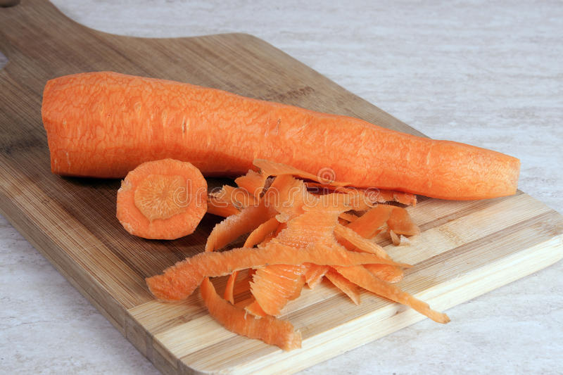 Peeled carrot on a wooden cutting board royalty free stock photos