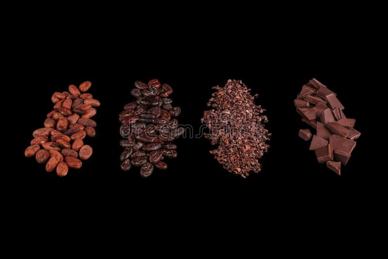 Peeled, chopped cocoa beans and  pile chopped, milled chocolate isolated on black background royalty free stock photo