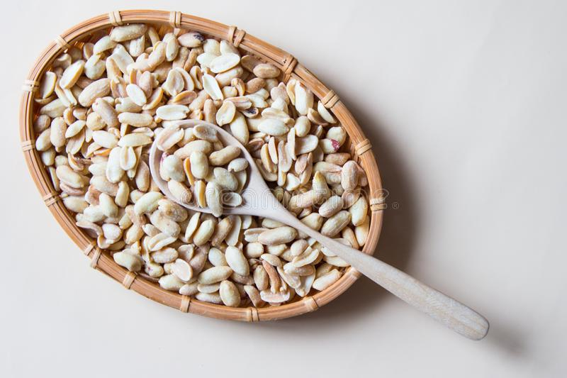 Peeled ha salato le arachidi in canestro di vimini e cucchiaio di legno su beige immagine stock