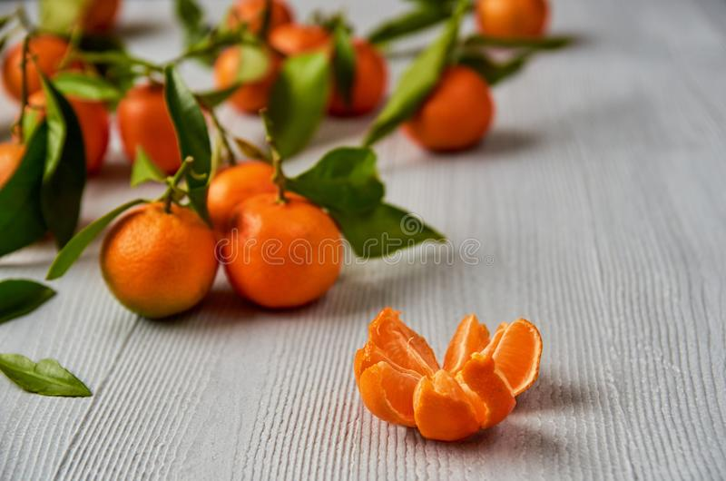 Peeled mandarin orange and juicy tangerine orange slices on the gray wooden board. Citrus background. Fresh raw tangerines stock photos