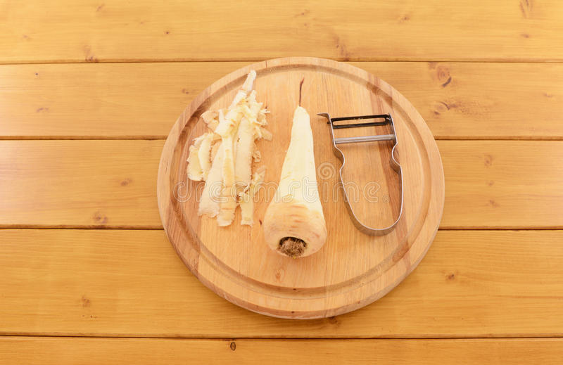 Peeled parsnip with vegetable peeler on a chopping board royalty free stock photography