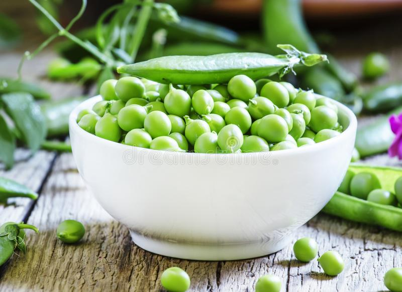 Peeled pea green peas in a white porcelain bowl, vintage wooden stock image