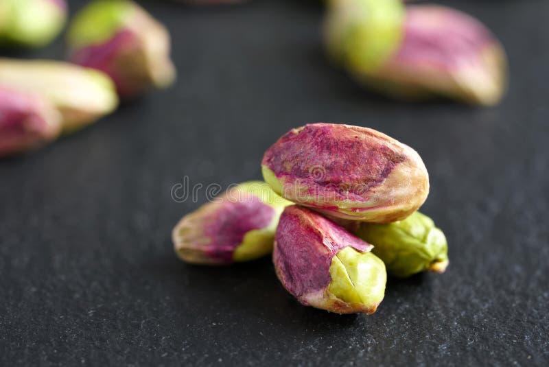 Peeled pistachios on the black stone board royalty free stock photos