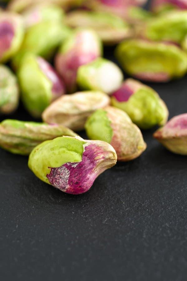 Peeled pistachios on the black stone board stock photo