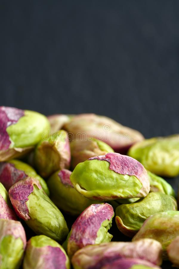 Peeled pistachios on the black stone board royalty free stock images