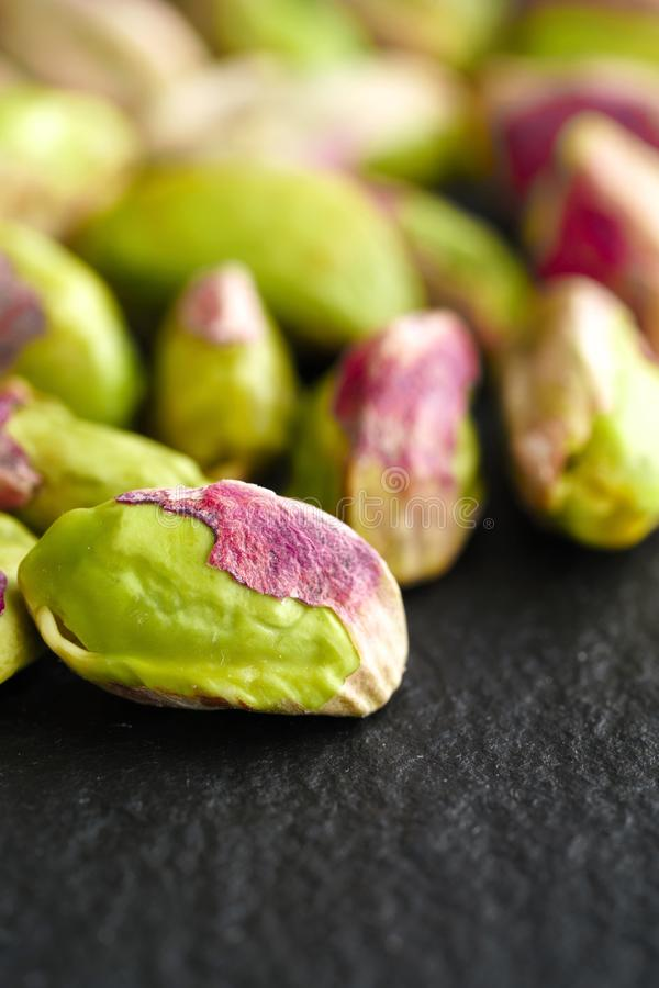 Peeled pistachios on the black stone board stock photography