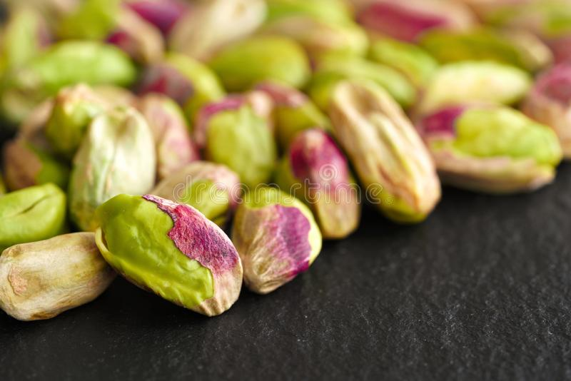 Peeled pistachios on the black stone board royalty free stock photo