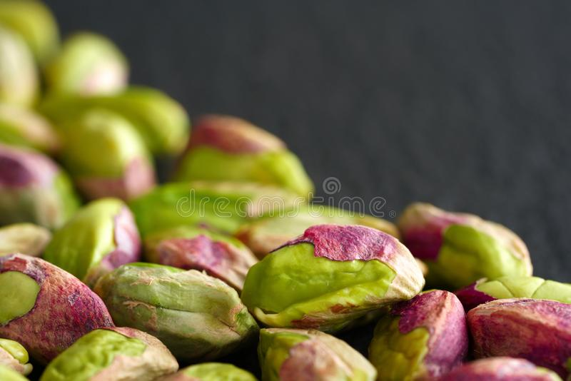 Peeled pistachios on the black stone board stock image