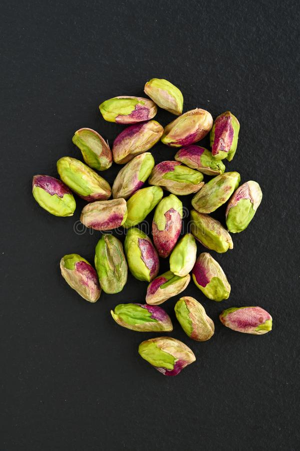 Peeled pistachios on the black stone board, top view royalty free stock images