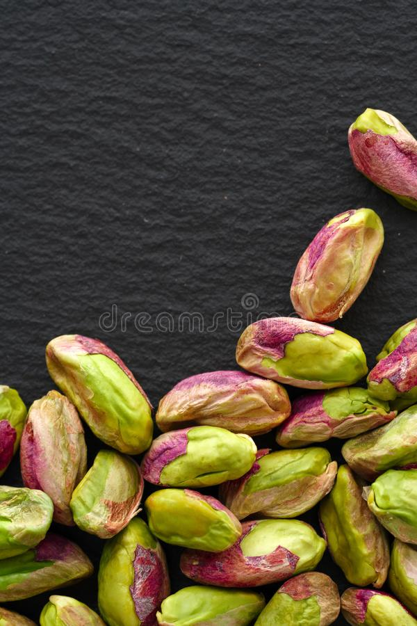 Peeled pistachios on the black stone board, top view stock photos