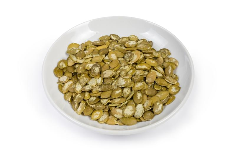 Peeled pumpkin seeds on saucer on a white background royalty free stock photo