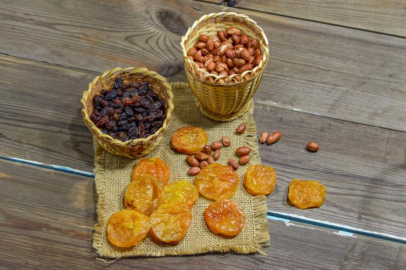 peeled raw peanuts dried apricots raisins on a wooden table background stock images