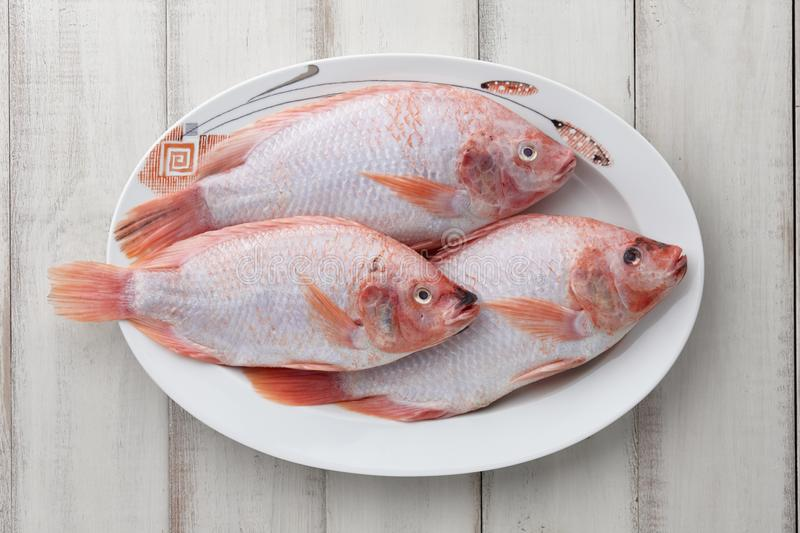 Peeled red tilapia in dish plate stock photos