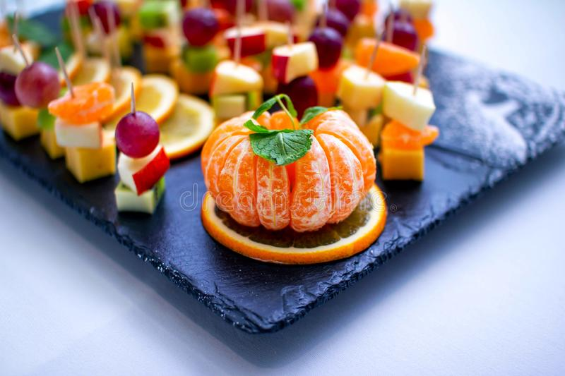 Peeled tangerine and fruit skewers - fresh apple, kiwi, lemon slices, grapes and cheese stock images