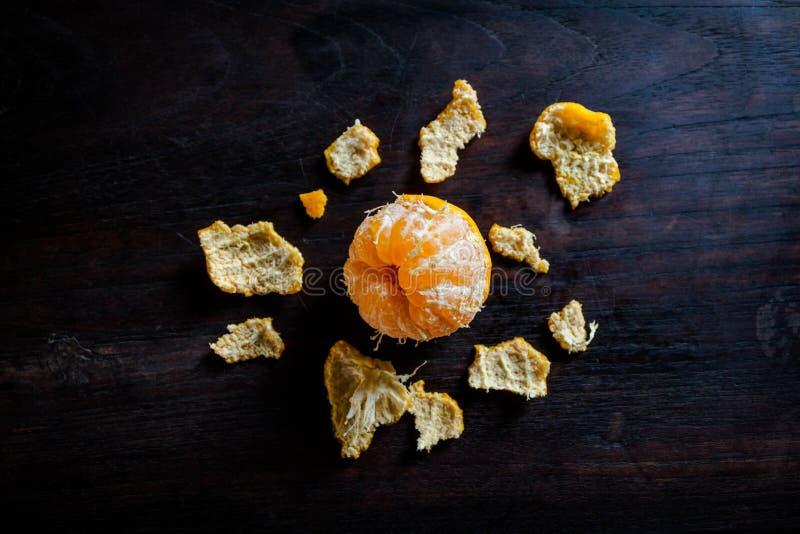 Peeled tangerines on dark wooden table royalty free stock photo