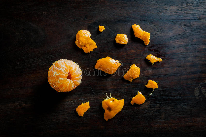 Peeled tangerines on dark wooden table stock photography