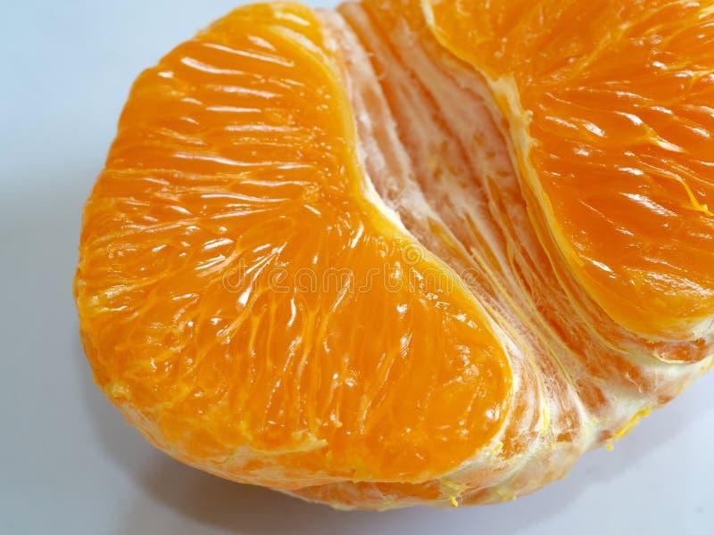 Peeled Tasty Sweet Tangerine Orange Mandarin Fruit. Mandarin lobule. Half of peeled tangerine or mandarin macro, part of fruit. Juicy ripe mandarin. Closeup royalty free stock images