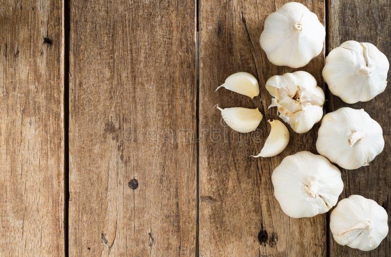 Peeled white garlic on brown wood table royalty free stock photos