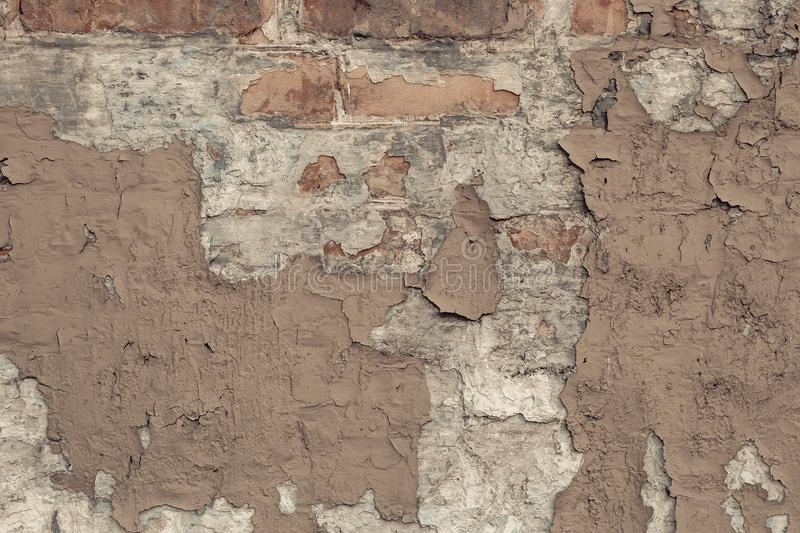 Peeling beige paint on a brick wall in vintage style. Vintage house facade. Empty space. Grunge background. old wall cement backgr. Ound. Light-brown shabby stock images