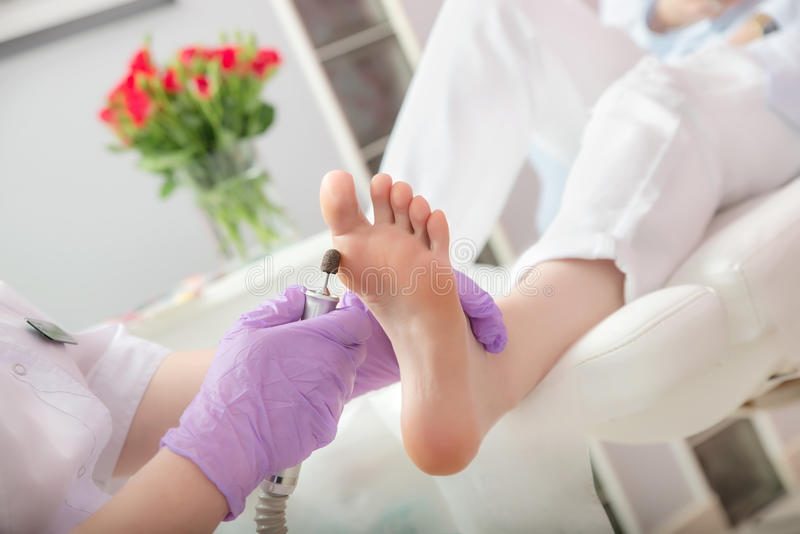 Peeling feet pedicure procedure with eletric device in the beau. Pedicure SPA procedure in the beauty salon. Peeling feet pedicure procedure. Electric apparatus royalty free stock photo