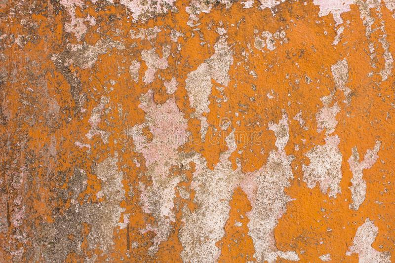 Peeling orange paint from light gray concrete wall with black spots of dirt and mold. rough surface texture. A peeling orange paint from light gray concrete wall stock images