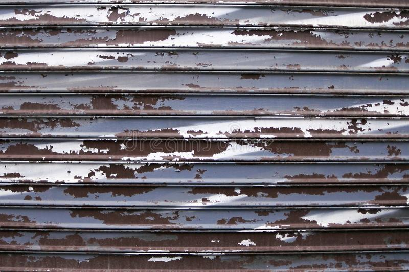 Peeling paint on an old iron fence. Grey background stock photos