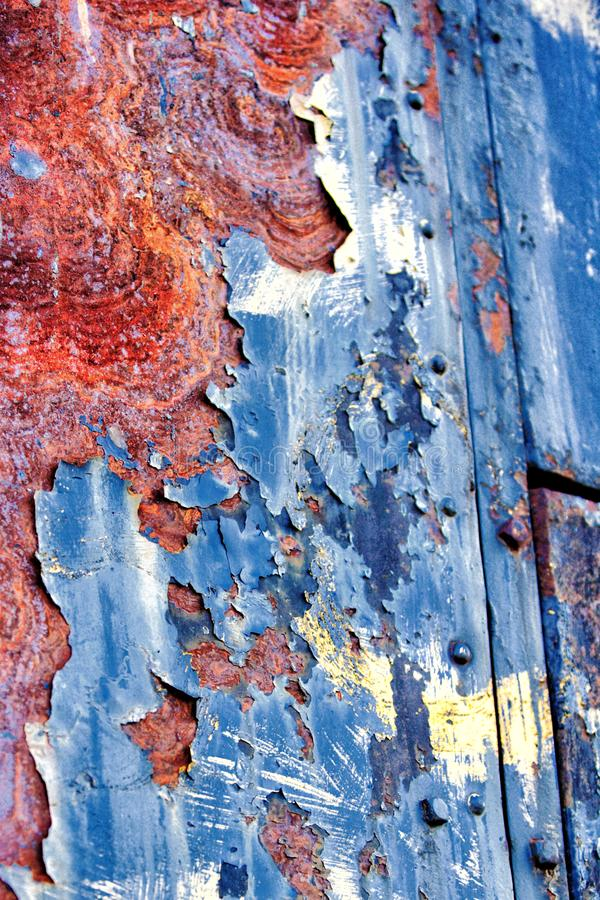 Peeling paint on a rusted metal surface. Paint peeling off a rusty metal bin at an old abandoned copper mine royalty free stock photo