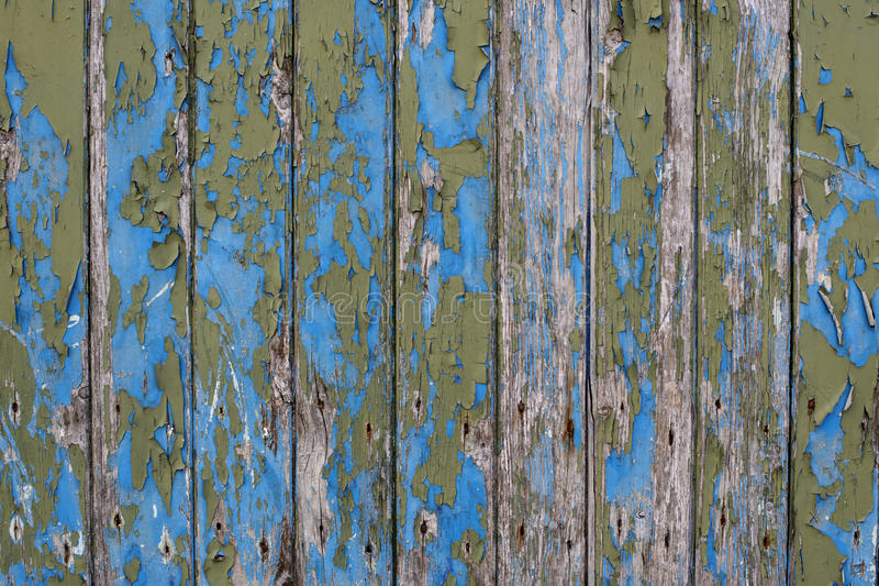 Peeling paint. Wooden door with peeling and faded blue and green paint royalty free stock photography
