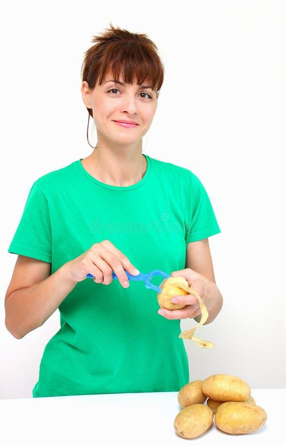 Peeling potato. A smiling woman peeling a potato isolated on a white background stock photos