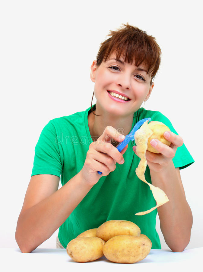 Peeling potato. A happy smiling woman peeling a potato isolated on a white background royalty free stock photo