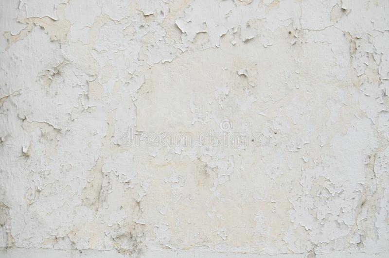 Peeling white old paint on an white cement wall texture for background and design art work. Peeling white old paint cracked wall as seamless pattern texture stock image