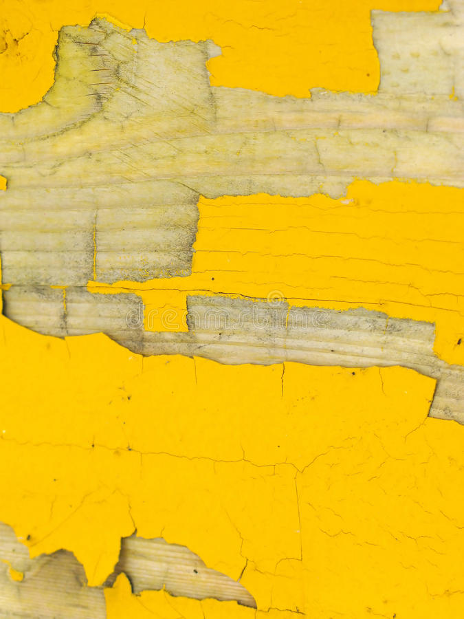 Peeling yellow paint on wood. Closeup view of yellow paint peeling from a wooden surface, exposing the natural wood stock photos