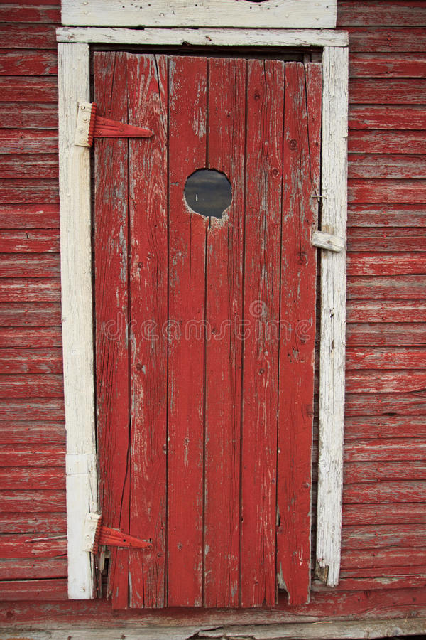 Peep hole in old red door stock photography