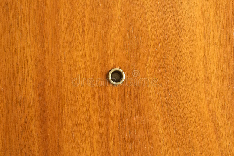 Peephole. Close up on peephole on wooden door stock images